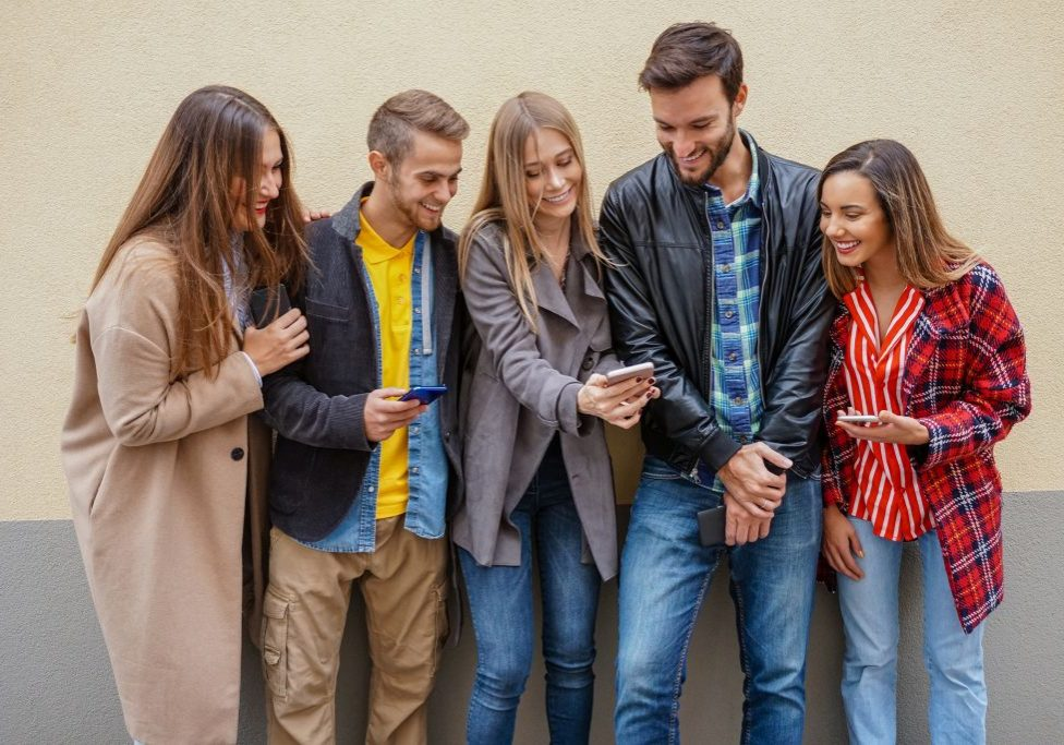 Young people using smartphones - Group of social media co workers having fun with online video photo - Technology obsession